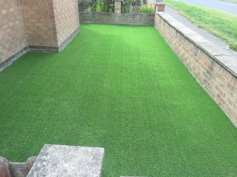 pet artificial grass laid at the side of a house